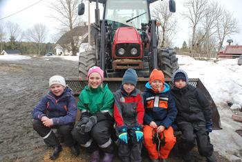 Barn sitter på traktor