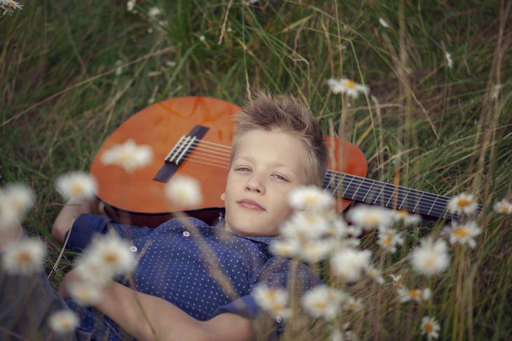Gutt i gresset med gitar