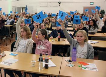 barn og ungdom viser stemmetegn på årsmøte