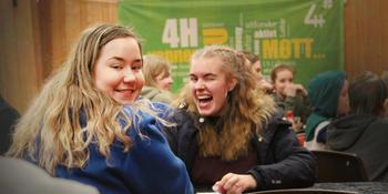 To jenter smiler, sitter ovenfor hverandre ved et bord.