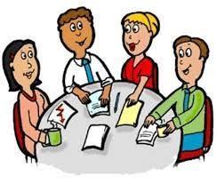 Mennesker sitter rundt et møtebord og tar notater