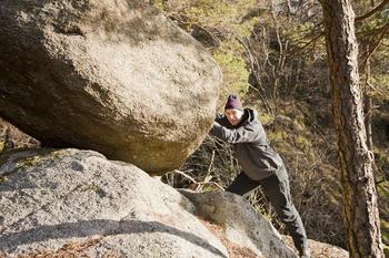 Mann dytter på stor stein