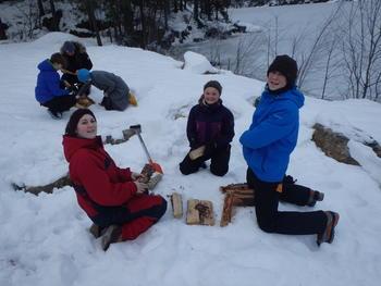 4H-medlemmer sitter i snøen og skal lage bål