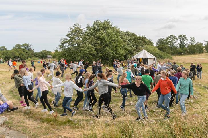 Ungdommer løper i ring rundt telt på 4H-leir