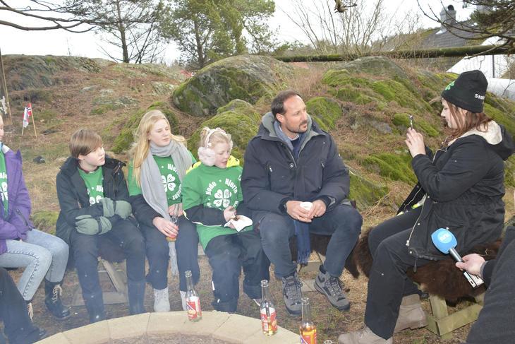 Barn og kronprinsen sitter rundt en bålplass, men ungdom filmer.