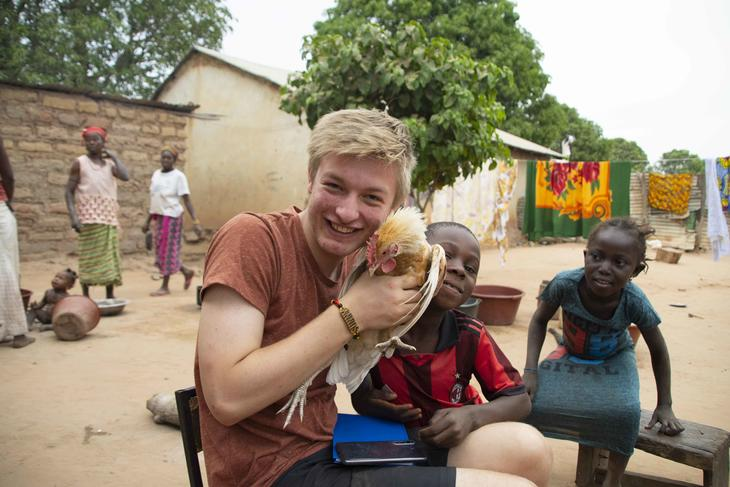 4H-er med dyr og gambiske barn i landsbyen.