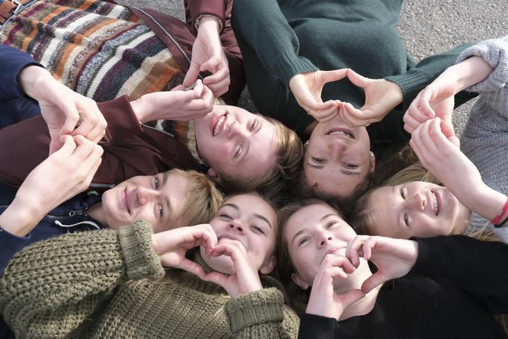Gruppe ungdommer ligger i ring og former hendene som hjerter.