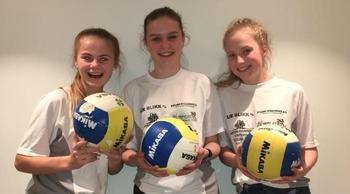 Tre glade jenter med volleyballer