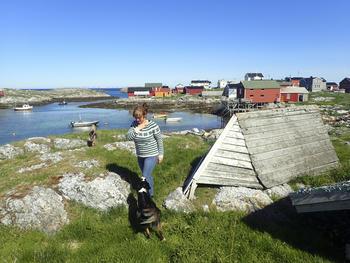Øya Givær utenfor Bodæ. Hus, kvinne, hund, sjæ, svaberg