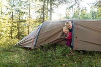 To barn titter ut av et telt.