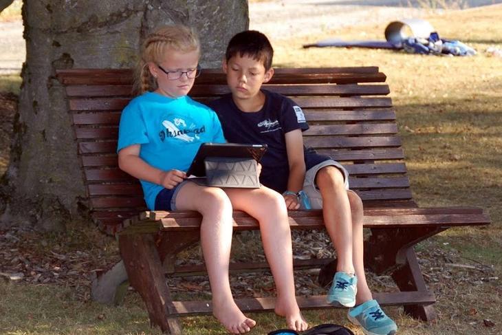 Gutt og jente på benk, foto: Toyni Tobekk