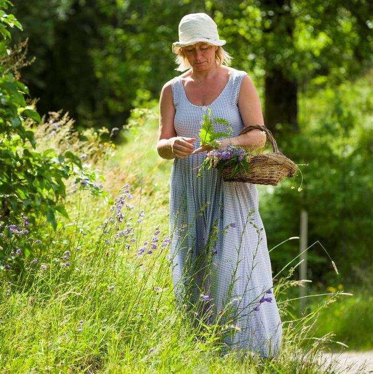 Dame plukker blomster langs en sti