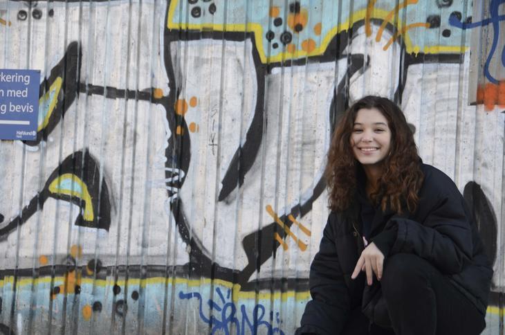 Jente foran murvegg med grafitti