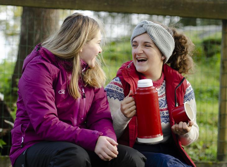 To unge jenter koser seg foran bålet med varm drikke.