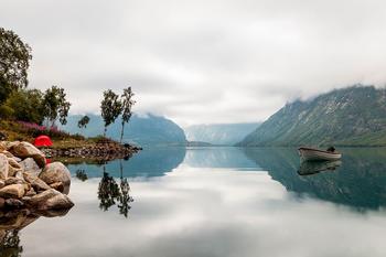 Båt på vannet, med fjell og telt i bakgrunnen