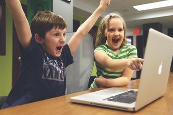 To barn som jubler bak datamaskin